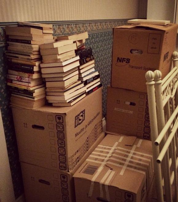 Muuttolaatikoita ja kirjapinoja olohuoneessa.
